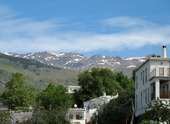 """LAS ALPUJARRAS: A more detailed view of the Sierra Nevadas. At the right of the photo, note the characteristic chimney pot which is a sort of trademark for the town. The region below the mountains is known as """"Las Alpujarras,"""" a name whose origin is in some dispute."""