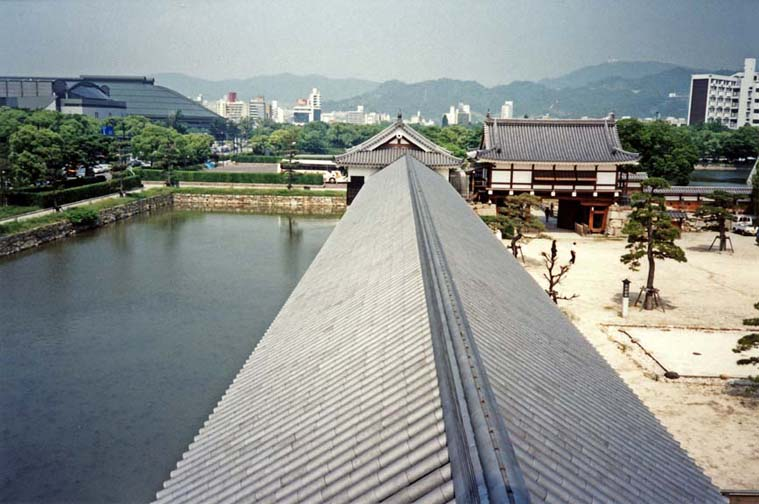 Moat running along the wall of the reconstructed Hiroshima Castle grounds, photographed from on top of the wall, which now encloses a museum. In the distance on the left, the Hiroshima baseball stadium. May 19, 1998