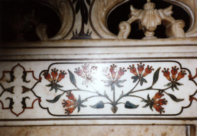 """Detail of the colored stone inlay in the chamber over the tomb of Mumtaz Mahal. 17th C. The further you penetrate into the mausoleum, the more delicate and rich the decoration becomes. The armed guard stationed to prevent photography inside the tomb instead passively watched me take this photograph and then extorted 50 rupees as """"fees."""" On the way out I noticed a sign warning visitors not to pay fees charged by anyone working at the tomb. Our only other encounter with government corruption was having the armed security guards extort bribes from us as we were screened leaving the country at the Calcutta airport. One of them asked me for a """"birthday present,"""" but I felt I'd paid my dues in Agra and refused--the only one to get through to the boarding area free."""