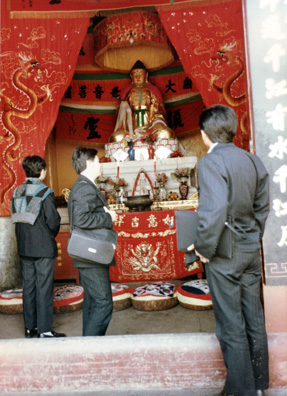 MT. EMEI: Usually we weren't allowed to photograph the Buddhas (most were being used for worship), but I shot this from the outside, with our guides in the foreground. The guy in the middle was kept telling us to hurry up and argued here with the monk who wanted to charge more to write Bonnie's name on a scarf in Chinese characters than he charged the locals. Then the guide pocketed the difference.