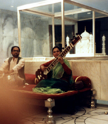 A tabla player and sitar player performing in the lobby of an Agra hotel in front of a model of the nearby Taj Mahal.
