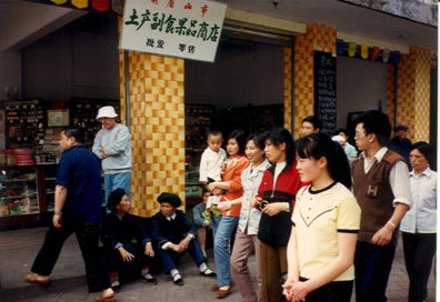 LESHAN: Three women in ethnic dress sitting in front of a shop (Doug Hughes standing in rear).