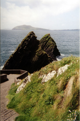 DINGLE PENINSULA: These striking rocks mark the boat landing where people can set off for the Blasket Islands (visible in the distance), now abandoned, but once occupied by a hardy group of folks who produced a striking number of fine books memorialized in the spectacular Blasket Centre in Dún Chaoin, where we viewed a film of the history of the islands. Because most of the audience was made up of an Irish-speaking local high school group, we had to wear headphones to hear an English translation. Much of the Dingle Peninsula is Gaeltacht, an area where Gaelic is promoted and sustained. We heard it used on the streets in Dingle, even by young people, quite casually.