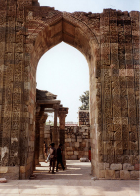 An elaborately carved stone archway, typical Mughal-style pointed arch gateway.