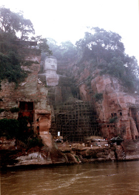 "LESHAN: We crossed by boat, then climbed to the top of the cliff behind the Big Buddha. Passing the first display we had seen dedicated to Chairman Mao, Mr. Cai confided to me that he was a Red Guard leader while in middle school, during the Cultural Revolution. ""It was a lot more fun than studying!"" He added later that a whole generation had been lost to the movement, with many talented people failing to get the educations they needed to succeed in careers. This was the biggest Buddha in the world until a businessman build a bigger one in Japan in modern times. It was badly corroded, perhaps from air pollution. The scaffolding had been erected for restoration purposes."