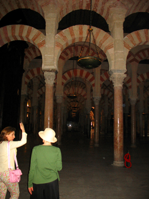 CORDOBA: A guide talks with Paula Elliot out a tour of the mosque. Because of the cathedral which blocks its center, few photographs show the full width of the mosque, but this shot suggests the building's size.
