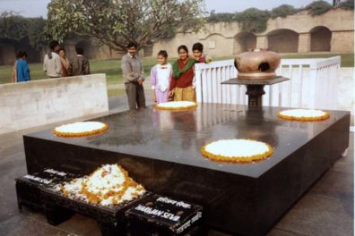 """This simple slab marks the spot where Mahatma Gandhi was cremated. It is decorated simply with flower petals. The donation boxes in the foreground accept donations to aid Gandhi's beloved Untouchables, whom he called """"harijans"""", """"Children of God."""""""
