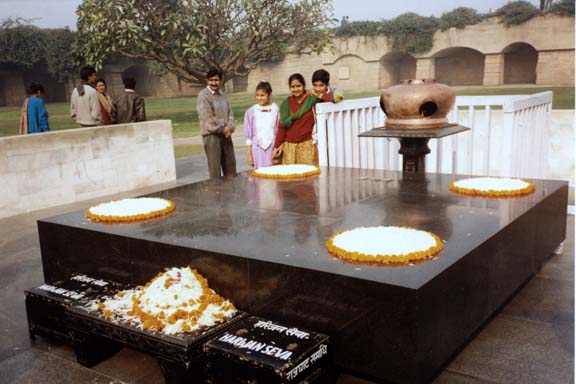 "This simple slab marks the spot where Mahatma Gandhi was cremated. It is decorated simply with flower petals. The donation boxes in the foreground accept donations to aid Gandhi's beloved Untouchables, whom he called ""harijans"", ""Children of God."""