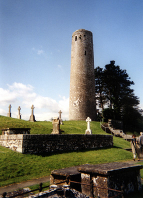"""CLONMACNOISE: We enjoyed our stay at the funky (and cheap) Bastion B&B in Athlone, but found little else to keep us in town. We were there to break our drive back east and to visit the Medieval site of Clonmacnoise (in Irish, """"Cluain Mhic Nóis), just to the south. It's a cluster of churches, towers, and other ruins overlooking the river Shannon, with a fine museum and interpretive center. It is said to have been founded by St. Ciarán in 548. This was a center of learning which between the 7th and 12th centuries drew scholars from all over Europe. Most of the ruins date from the 10th-12th centuries. Above, the 65-foot tall O'Rourke's Tower (Irish """"O Ruairc""""), named after a high king of Connaught. Several Irish high kings were buried here."""