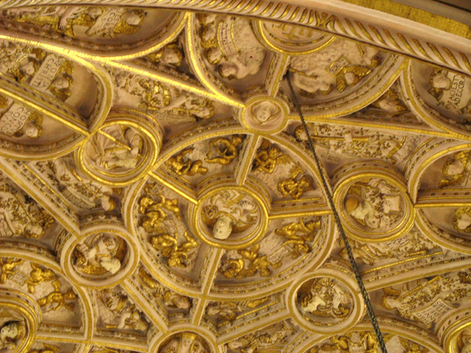 CORDOBA: Detail of the gilded dome over the altar of the small cathedral built inside La Mezquita. toward the top of the picture, angels read from a musical score.