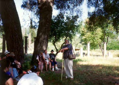 OLYMPIA: After waiting for a long-winded French tour guide to finish her lecture, we moved into the site of the Palaestra (and more important, the shade of a large tree), to have Don give us a very interesting lecture about Greek mathmatics as his leaned on the Greek shepherds' crook he had bought to use as a walking stick in Andritsina.