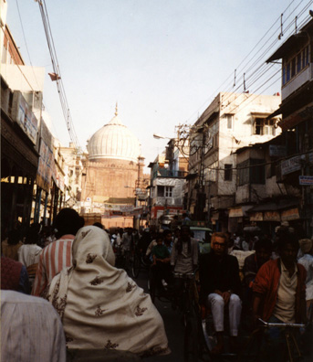 "The largest mosque in India is the Jami Masjid (Friday Mosque) in the old part of Delhi. Built by Shah Jahan, 1650-66. Photograph made from a pedicab going through the streets nearby. That evening, Terry and our family had dinner and visited with Vijay and Sarita Aggarwal in a Delhi suburb--old friends from their time in Pullman. Our inexperienced taxi driver had a terrible time finding the address, but we had a very pleasant evening's conversation. Like all the Hindus we spoke with, Vijay insisted that the recent ""communal"" violence had been the product of unscrupulous manipulation by politicians and that Muslims and Hindus still regarded each other as friends. We did not get to hear any Muslim opinions; but clearly educated Hindus were deeply ashamed of the violence, though a few showed signs of not entirely disapproving of the goal of tearing down some major mosques to rebuild ancient temples: they just wanted it done peacefully. Indian unity still seems a long way off."