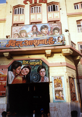 "One of the many theaters showing ""Bollywood"" films--popular films made principally in Bombay. All of them contain musical numbers which are the main source of pop music in India."
