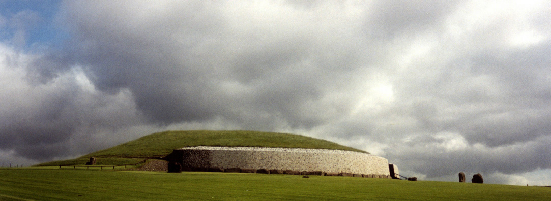 Brú na Bóinne: Our tour bus picked us up the next morning near our B&B and took us first to the most famous of the mounds, Newgrange, with its nearby visitor center and museum. Entry to the site is permitted only with authorized tours, but they are well worth the cost. We got the first tour of the day, so the site was relatively uncrowded. The Newgrange Mound measures 262 feet across and almost 43 feet high. Like the other principal mounds in the area, much of it was constructed using enormous non-native stones brought laboriously from far away by large teams of hard working stone-age inhabitants around 3200 BCE, long before the Egyptian pyramids were built. Stonehenge in England is over a millennium more recent.
