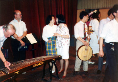 SZECHUAN MUSIC CONSERVATORY: Then followed a great concert of traditional folk music (some in modern arrangements) by faculty and students. Afterwards, we were invited on stage to try out the instruments. Above left, Doug examines a gu-zheng. Above right, musician holding a ruan.
