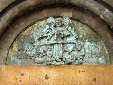 BUDAPEST: The carving over the door shows an angel, rather than the usual figure of Christ, weighing out the sins of humanity at the Last Judgment. Note the demon at work on the angel's left (your right), where the damned are always located.