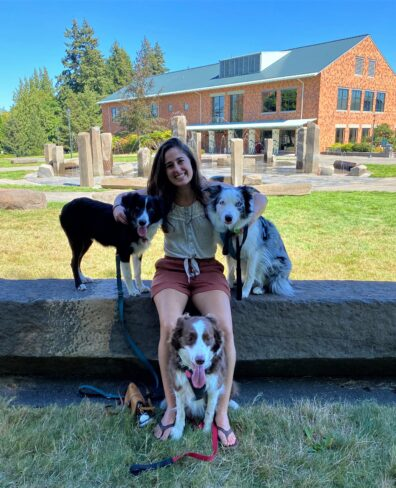 Kelsey Pascoe sitting with her three border collies
