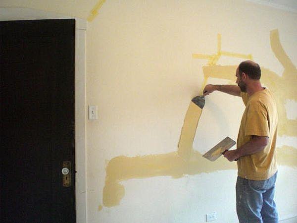 """This worker is applying """"mud"""" to repair sheetrock wall"""
