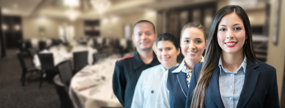 four people in line smiling at camera - restaurant dining room in background