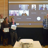 Photo: Members stand in front of screen during Psi Chi Induction award ceremony.