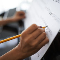 Photo: Closeup of hand holding pencil, writing sheet music propped against piano.