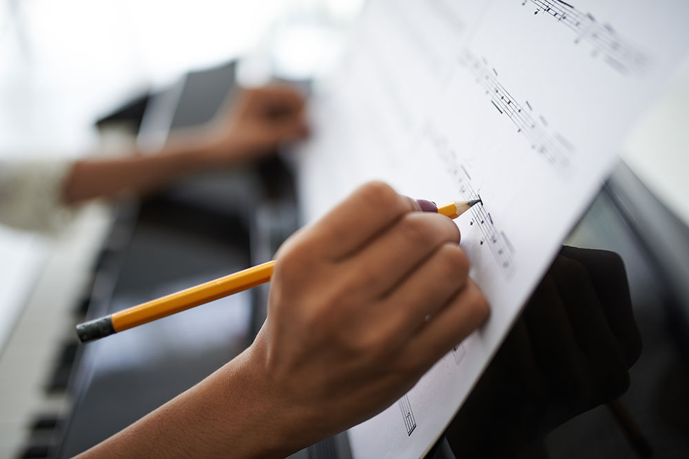 Photo: Closeup of person's hand adding notations to sheet music propped on piano music stand.