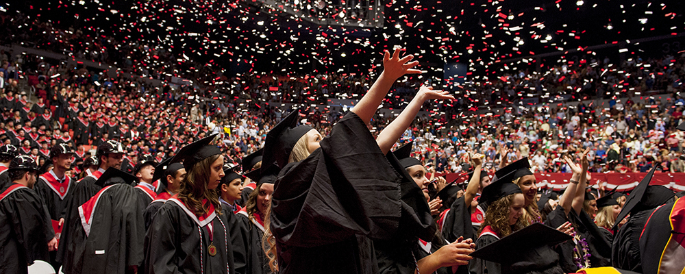 Photo: Student raises hands to confetti at graduation ceremony.