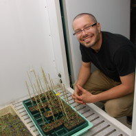 ARCS Scholar Matt Marcec kneeling down in front of plants