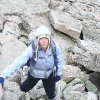 Grad Student Rachel DeTar posing in winter gear on top of rocky terrain