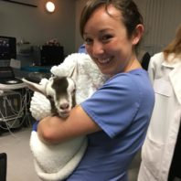 Graduate student holding baby goat