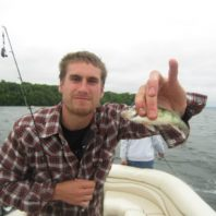 graduate student holding small fish in fingers