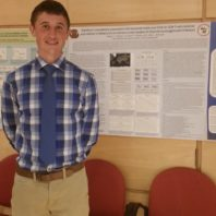 graduate student standing in front of poster