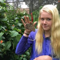 female graduate student holding large moth