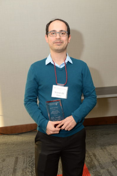 an award recipient poses with his award