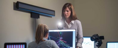 Dr. Georgina Lynch with a flashlight in the face of a student at a computer