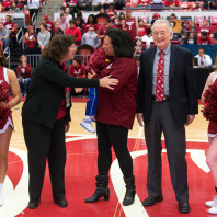 Washington State University co-provosts Erica Austin, left, and Ron Mittelhammer honor Paula Groves Price for her academic and teaching excellence during a media timeout in the first half of the Cougars' Feb. 3 basketball game at Beasley Coliseum.