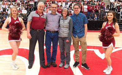 Washington State University co-Provost Ron Mittelhammer, second from left, honors faculty member Jeff Joireman, accompanied by his wife, Esther, and son Joshua during a first half media timeout in the Cougars' game against California Sunday, Feb. 21 at Beasley Coliseum.