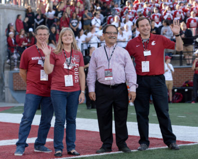 Faculty members Terri Levien, second from left, and Martin Maquivar wave to the crowd after being honored by Provost Dan Bernardo, center, during the Sept. 3 football game at Martin Stadium.