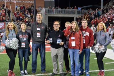 John Petrie, third from left, and Maureen Schmitter-Edgecombe, third from right, are honored by Provost Dan Bernardo, center, during the Cougars' victory over Cal on Nov. 12.