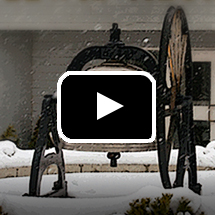 cougar bell in snow in background, video play button in foreground