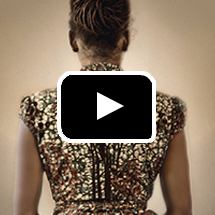 back view of woman's upper body in gold dress in background, video play button in foreground