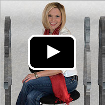 smiling woman on stool in background, video play button in foreground