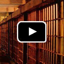 jail cells in background, video play button in foreground