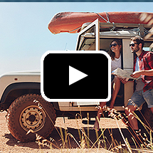 man holding map and woman in open door of jeep in background, video play button in foreground