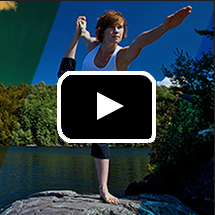 woman outdoors in yoga dancer pose in background, video play button in foreground