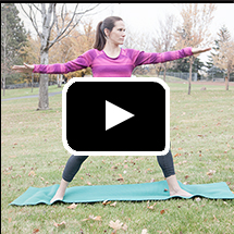 woman in yoga warrior two pose in background, video play button in foreground