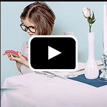 child in big glasses holds cell phone next to formally-set table in background, video play button in foreground