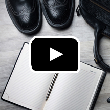 overhead view of shoe tips, open notebook and pen, handle of bag, in background, video play button in foreground