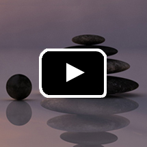 stacked flat smooth rocks, one round rock, reflected in wet sand in background, video play button in foreground