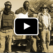 sepia toned men in dark  glasses and goggles stand next to truck in desert in background, video play button in foreground